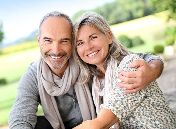 Older man and woman smiling outdoors