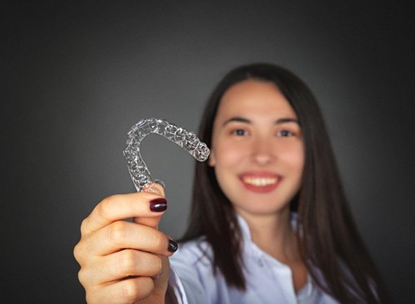 Happy woman smiling and holding Invisalign on black background