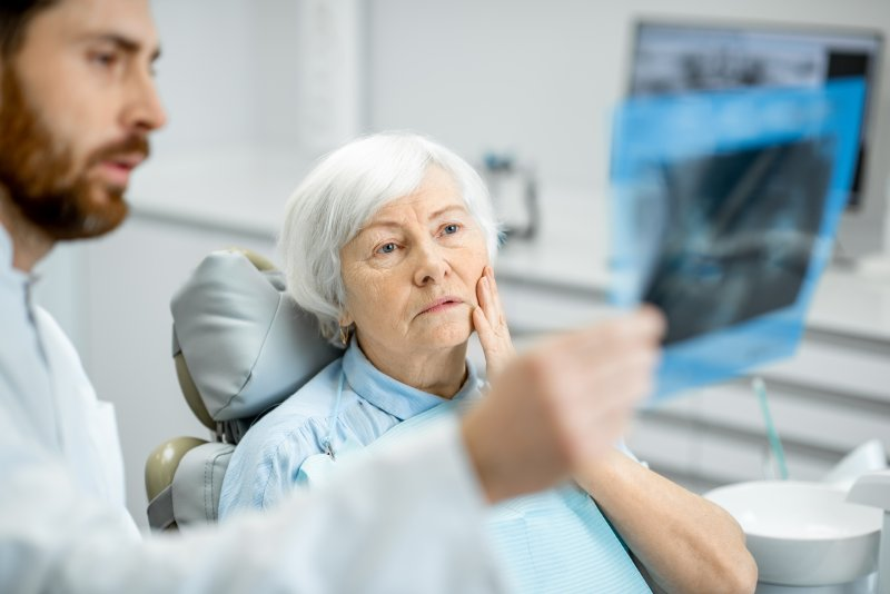 Dentist showing woman with dental implants her X-rays